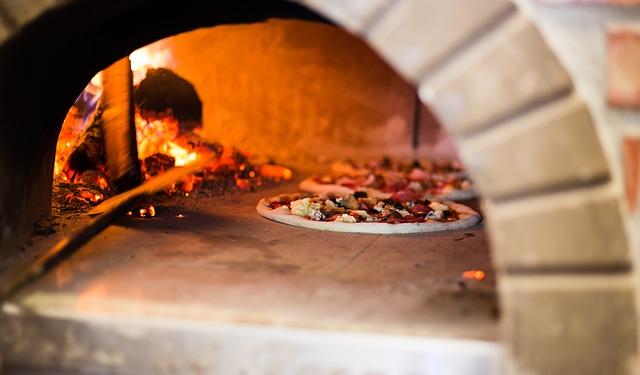 La cuisson d'une pizza dans un magnifique four à pizza professionnel.